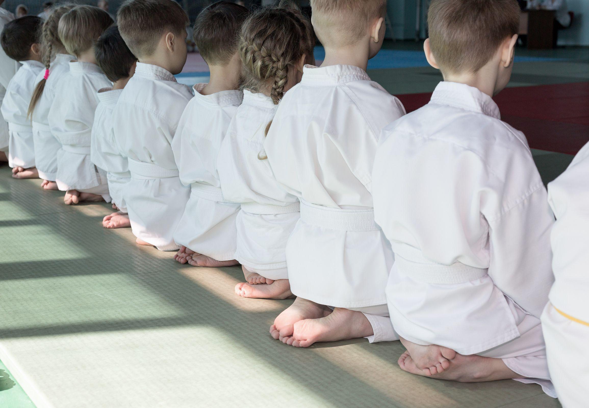 Group of children in kimono sitting on tatami on martial arts training seminar